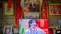 FILE - A television shows a broadcast of a Chinese talk show program as it sits beneath a photo of Chinese President Xi Jinping in a home converted into a tourist homestay in Zhaxigang village in western China's Tibet Autonomous Region, June 4, 2021.