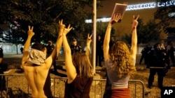 美國共和黨總統參選人川普星期二晚上在新墨西哥州舉行競選集會時,抗議者遭警察隔在鐵馬外圍。