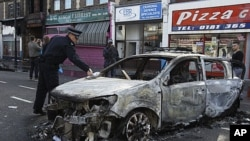 A police officer removes identification from a police car set on fire and burnt during riots in Tottenham, north London, August 7, 2011