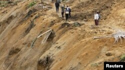 Residents walk along a path in an area affected by a landslide after an earthquake struck in Koto Timur district in Padang Pariaman, a port city sits atop one of the world's most active seismic fault lines along the Pacific 'Ring of Fire', October 3, 2009