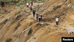 Cư dân đi bộ dọc theo con đường trong một khu vực bị ảnh hưởng vì đất lở sau một vụ động đất tại huyện Koto Timur, Tây Sumatra