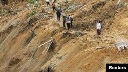 Warga berjalan di jalan setapak di wilayah yang terkena bencana tanah longor di Koto Timur,Padang Pariaman (Foto: dok). Dua buah insiden tanah longsor dilaporkan terjadi di wilayah Sumatera, menewaskan sedikitnya sembilan orang dan 17 orang dinyatakan hilang (26/1).