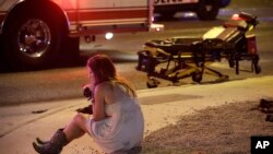 FILE - In this Oct. 2, 2017, file photo, a woman sits on a curb at the scene of a shooting outside of a music festival along the Las Vegas Strip. Months after Facebook and Google announced major efforts to curb the spread of false stories masquerading as news, it's still cropping up, most recently in the wake of the Las Vegas mass shooting.