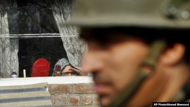 A Kashmiri woman watches from inside her home window an Indian policeman stand guard during a protest on the outskirts of Srinagar, India, Jan. 8, 2013.
