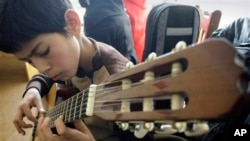 An Afghan student practices playing the guitar in a class.