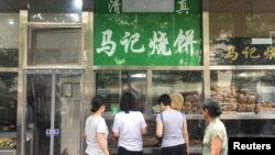 The Arabic script on the signboard of a halal food store is seen covered, at Niujie area in Beijing, China, July 19, 2019.REUTERS