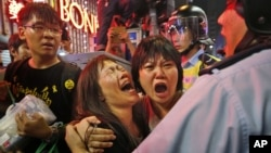 Protesters cry as the police officers try to stop them blocking the road in Mong Kok district of Hong Kong, Nov. 26, 2014.