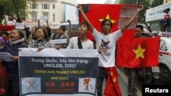Warga Vietnam membawa bendera nasional mereka dan spanduk yang menyatakan seruan mereka saat menggelar aksi protes anti-Tiongkok di jalanan kota Hanoi, Minggu (9/12).