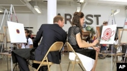 Catherine, Duchess of Cambridge smiles as her husband Britain's Prince William comments on her artistic skills during a visit to the Inner City Arts campus in Los Angeles, July 10, 2011