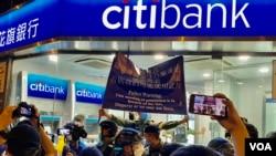 8-31事件一周年,一批警員衝入太子地鐵站出口附近一間銀行分行,高舉旗幟警告在場人士涉嫌非法集會。(美國之音湯惠芸攝)