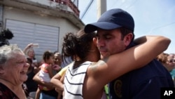 Governor Ricardo Rossello receives a hug from a resident after the arrival of National Guard at Barrio Obrero to distribute water and food among those affected by Hurricane Maria, in San Juan, Sept. 24, 2017.