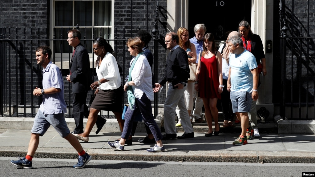 Victims of the Grenfell apartment tower block fire and volunteers leave 10 Downing Street after a meeting with Britain's Prime Minister Theresa May in London, June 17, 2017.
