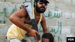 Pejuang anti-Gaddafi (kiri) mencoba menenangkan anggotanya saat pasukannya sulit menembus pertahanan Gaddafi di Sirte (27/9).