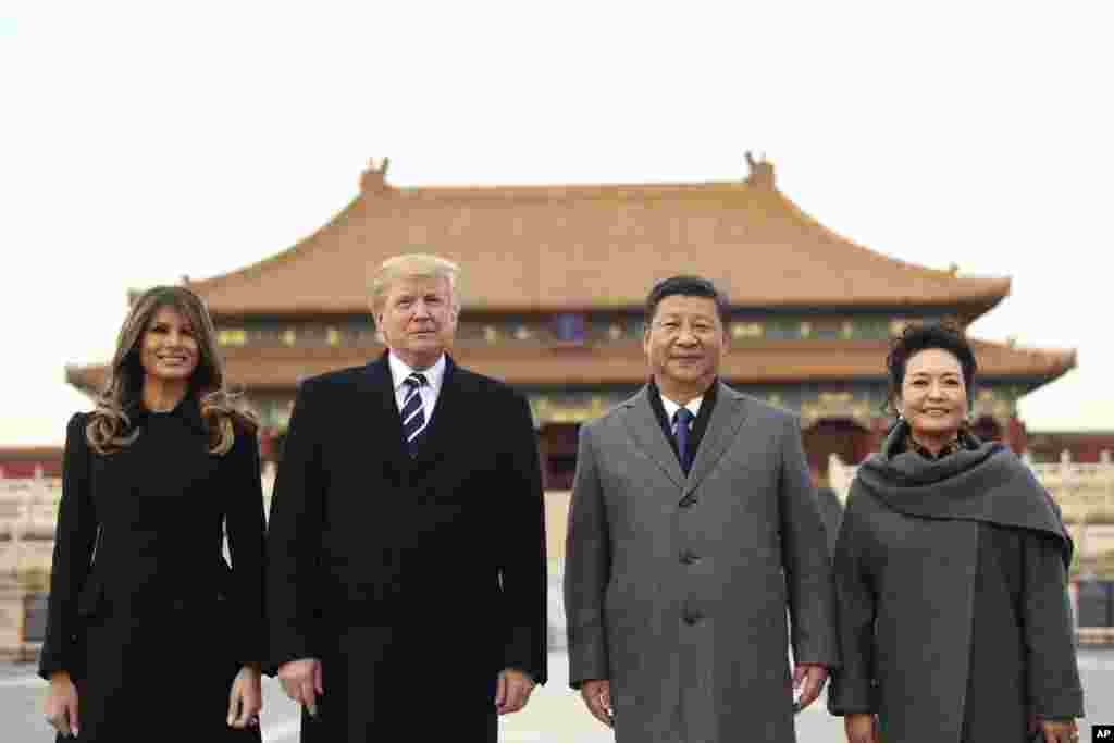 President Donald Trump, second left, first lady Melania Trump, left, Chinese President Xi Jinping, second right, and his wife Peng Liyuan, stand together as they tour the Forbidden City in Beijing, Nov. 8, 2017.