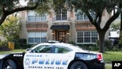 Un auto de la policía vigila la entrada a la residencia de la enfermera que dio positivo por ébola en Dallas.