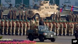 FILE - Pakistan's President Mamnoon Hussain, center on a military vehicle, reviews a military parade to mark Pakistan's Republic Day, in Islamabad, Pakistan, March 23, 2017.