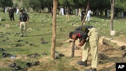 Pakistani police officers collect evidence at the site of a deadly suicide bombing in Shina Samar Bagh in Lower Dir, Pakistan, September 15, 2011.