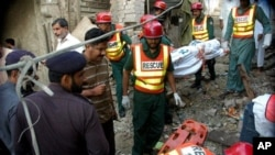 Pakistani police officers visit the site of explosion as rescue workers remove a dead body after a bomb blast in the shrine of Sufi Farid Shakar Ganj in Pak Pattan, some 200 kilometers (125 miles) west from Lahore, Pakistan on Monday, Oct. 25, 2010. A bom