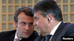 French Economy Minister Emmanuel Macron (L) and Germany's Economy Minister Sigmar Gabriel attend a news conference to present the Franco-German report on economic reforms and investment at the Bercy Finance Ministry in Paris, Nov. 27, 2014.