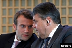 FILE - French Economy Minister Emmanuel Macron (L) and Germany's Economy Minister Sigmar Gabriel attend a news conference to present the Franco-German report on economic reforms and investment at the Bercy Finance Ministry in Paris, Nov. 27, 2014.