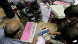 FILE - Indian election officials inspect electronic voting machines and other polling material prior to leaving for their respective polling booths ahead of the third phase of voting to the West Bengal state Assembly elections in Kolkata, India.
