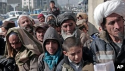 FILE - Afghan men and boys wait in line to receive donated sacks of wheat distributed by the World Food Program in Kabul, Afghanistan, Dec. 15, 2013.