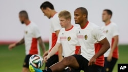 Belgium's captain Vincent Kompany, second right, who is recovering from an injury, keeps a ball up as he takes part in a training session at Estadio Manoel Barradas the day before the World Cup round of 16 soccer match against Belgium, June 30, 2014.