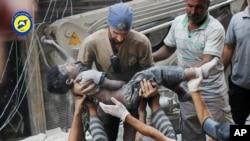 نیروهای امدادی در حلب در حال انتقال یک کودک مجروح پس از حملات هوایی به این شهر