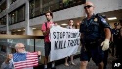 Polisi Capitol Hill berjalan di depan kelompok pengunjuk rasa yang memprotes RUU layanan kesehatan Partai Republik di Washington.