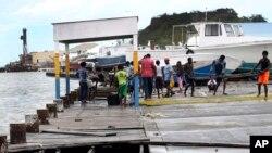 Masyarakat sedang menyelamatkan bagian-bagian dari pelabuhan yang rusak dihantam Badai Irma di Antigua dan Barbuda, 6 September 2017.