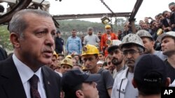 In this photo released by the Turkish Prime Minister's Press Office, Turkish Prime Minister Recep Tayyip Erdogan is surrounded by security members as he visits the coal mine in Soma, Turkey, May 14, 2014.