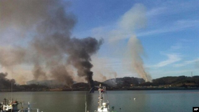 This picture taken by a South Korean tourist shows huge plumes of smoke rising from Yeonpyeong island in the disputed waters of the Yellow Sea on November 23, 2010. North Korea fired dozens of artillery shells onto a South Korean island, setting of an exc