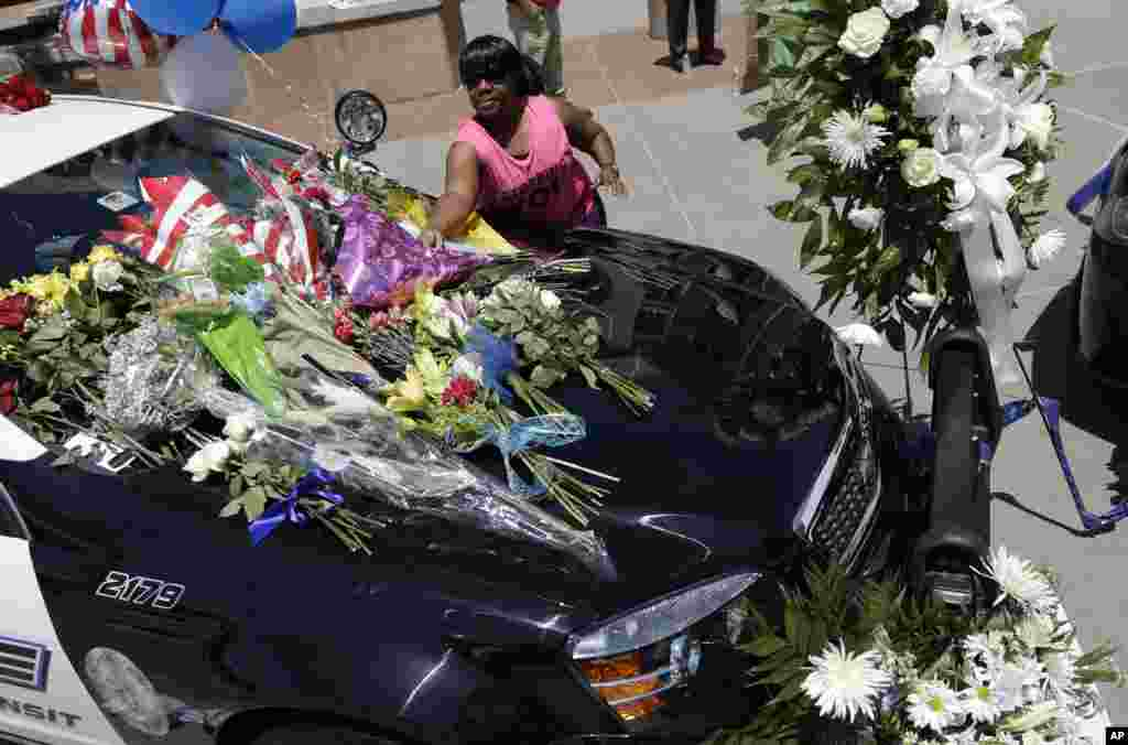 Cynthia Ware places flowers on a makeshift memorial at the Dallas police headquarters, July 8, 2016, in Dallas.