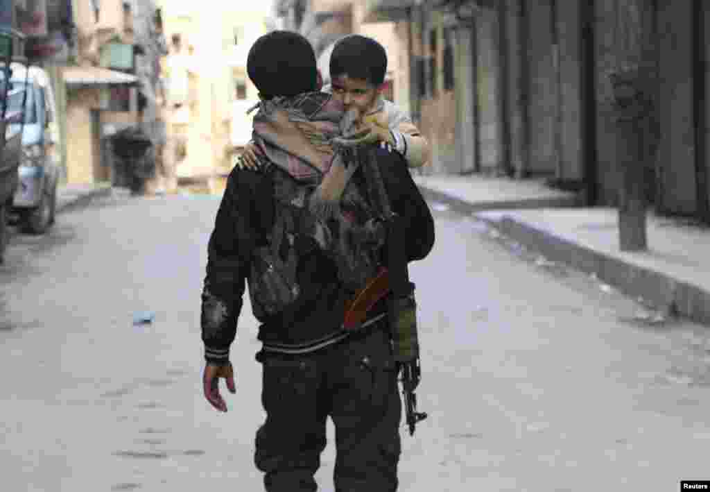 A Kurdish fighter from the Popular Protection Units (YPG) carries his son as he walks along a street, Sheikh Maqsoud neighborhood, Aleppo, Feb. 18, 2014.