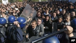 Algerian students scuffle with riot police officers near the Ministry of Higher Education in Algiers, February 21, 2011