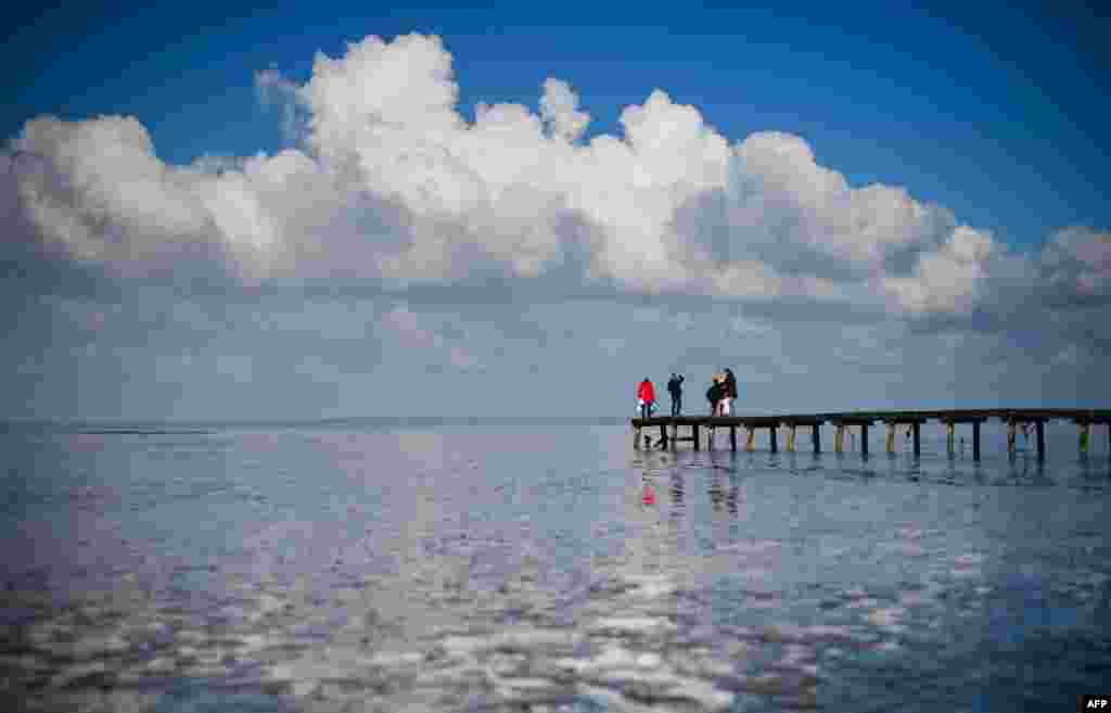 People stand on a bridge at the Jadebusen (Jade Bay) in Dangast on the North Sea coast, northwestern Germany.