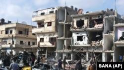 Des Syriens sur la scène des deux explosions dans le quartier pro-régime de Zahraa, dans la province de Homs province, en Syrie, le 21 février 2016. (SANA via AP)