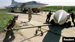 "Ground stuff tow a cruise missile towards Tupolev-22 ""Backfire"" plane for loading at a military base near the city of Ussuriysk in this September 17, 1999 file photo."
