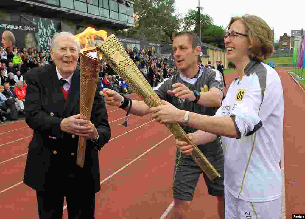 Roger Bannister (L) passes the Olympic flame to torchbearer Nicola Byrom during the London 2012 Olympic Games torch relay at the Iffley Road Stadium in Oxford, southern England July 10, 2012.