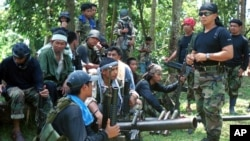 In this undated file photo, Abu Sayyaf spokesman Abu Sabaya, right foreground, stands with militants in Basilan, the Philippines.