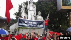 Protesters chant anti-China slogans while standing at a war martyrs monument during an anti-China protest in Hanoi, July 1, 2012.