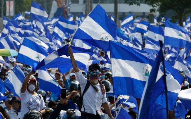 니카라과 수도 마나과에서 정부 탄압에 항의하는 시위대가 자국 국기를 흔들고 있다.
