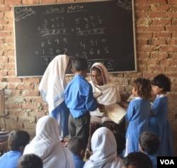 ایک دیہی اسکول میں ٹیچر بچوں کو پڑھا رہی ہے۔