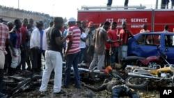 人们聚集在尼日利亚阿布贾一处汽车站的爆炸现场。(2014年4月14日)