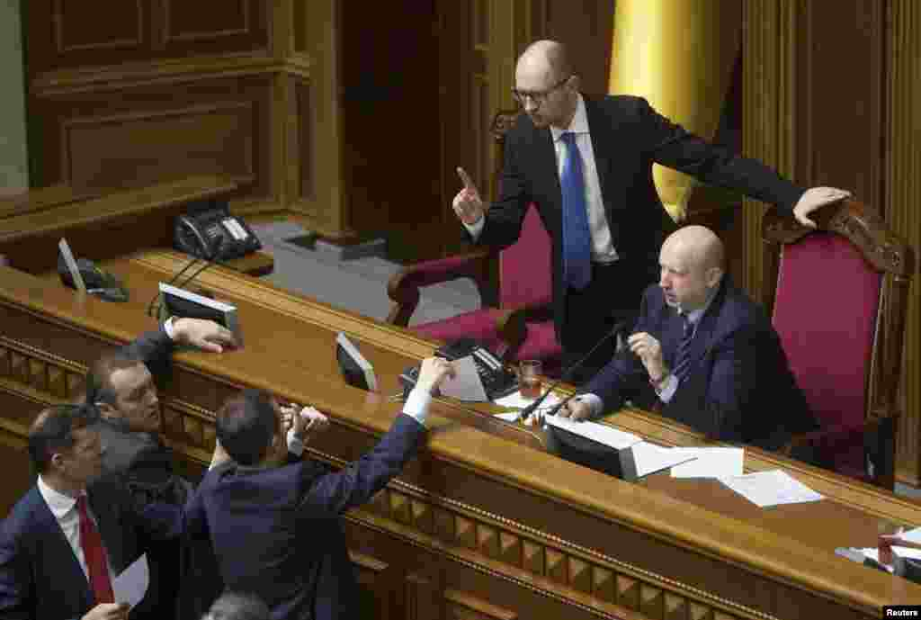Ukrainian Prime Minister Arseniy Yatsenyuk (top left) speaks at a parliament session saying the price Ukraine pays for Russian gas supplies would rise 79 percent, pushing Ukraine towards economic disaster.