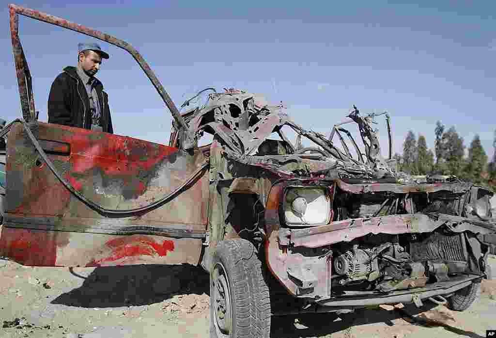 An Afghan police officer inspects a vehicle damaged at the scene of a suicide attack at the gate of an airport in Jalalabad, Nangarhar province on February 27, 2012. (AP)