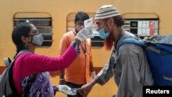 印度一名卫生工作者在孟买一个列车站为旅客量体温(路透社2021年4月7日)