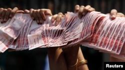 3月28日,泰國反政府抗議者手舉準備捐出泰銖,作為支持反政府素貼。