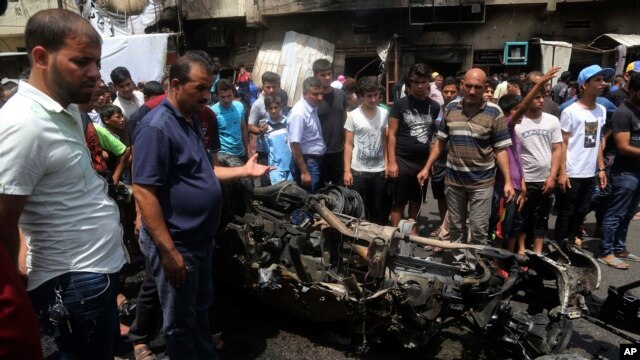 FILE - Citizens inspect the scene after a car bomb explosion at a crowded outdoor market in the Iraqi capital's eastern district of Sadr City, Iraq, May 11, 2016.
