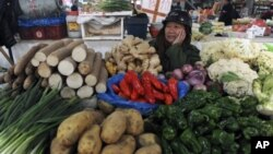 A vendor waits for customers at his vegetable stall at a market in Hangzhou, Zhejiang province, January 12, 2012. China's inflation rate eased to a 15-month low in December, though food prices are a reminder of the risks the government is weighing as it t